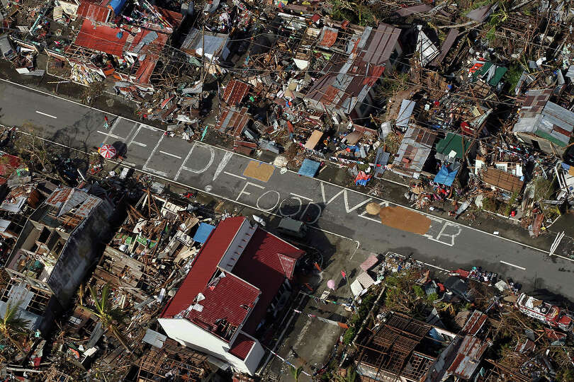 An aerial view shows signs for help and food amid the destruction left from Typhoon Haiyan in the co