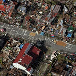 An aerial view shows signs for help and food amid the destruction left from Typhoon Haiyan in the coastal town of Tanawan, central Philippines, Wednesday, Nov. 13, 2013. Typhoon Haiyan, one of the strongest storms on record, slammed into six central Philippine islands on Friday leaving a wide swath of destruction and thousands of people dead.