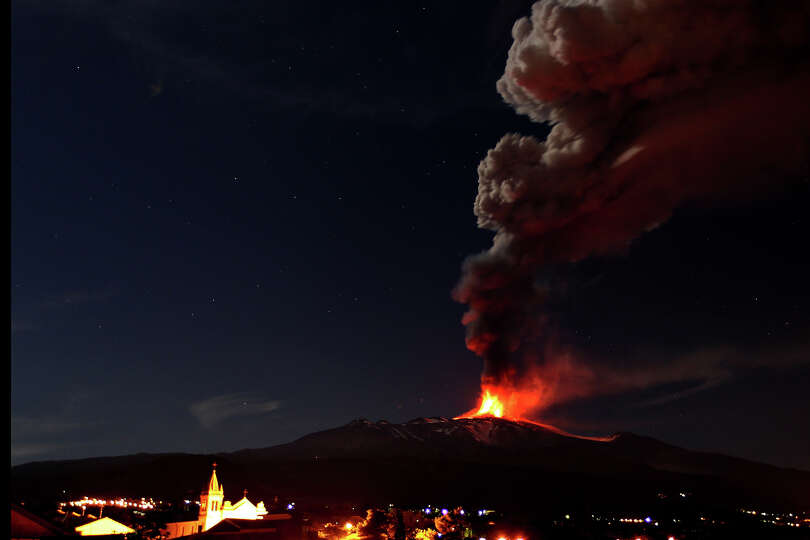 Mt. Etna, Europe's most active volcano, spews lava as smoke billows during an eruption as seen from
