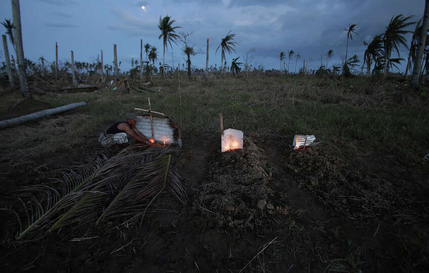 A survivor lights candles on a makeshift grave site of his father and uncle, left, on a field in Pal