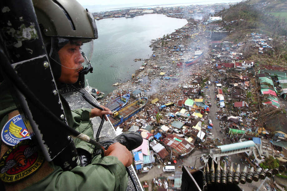 A Philipine Air Force crew looks out from his helicopter as Typhoon Haiyan-ravaged city of Tacloban is seen in the background, during a flight to deliver relief goods in Leyte province, Philippines, Tuesday, Nov. 19, 2013. Hundreds of thousands of people were displaced by Typhoon Haiyan, which tore across several islands in the eastern Philippines on Nov. 8. Photo: Dita Alangkara, ASSOCIATED PRESS / AP2013