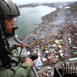 A Philipine Air Force crew looks out from his helicopter as Typhoon Haiyan-ravaged city of Tacloban is seen in the background, during a flight to deliver relief goods in Leyte province, Philippines, Tuesday, Nov. 19, 2013. Hundreds of thousands of people were displaced by Typhoon Haiyan, which tore across several islands in the eastern Philippines on Nov. 8.