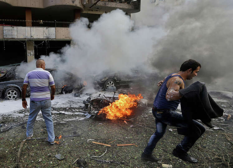 A Lebanese man runs in front of a burned car, at the scene where two explosions have struck near the