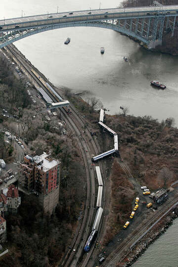 A Metro-North passenger train lays on it's side after derailing in the Bronx borough of New York, Su