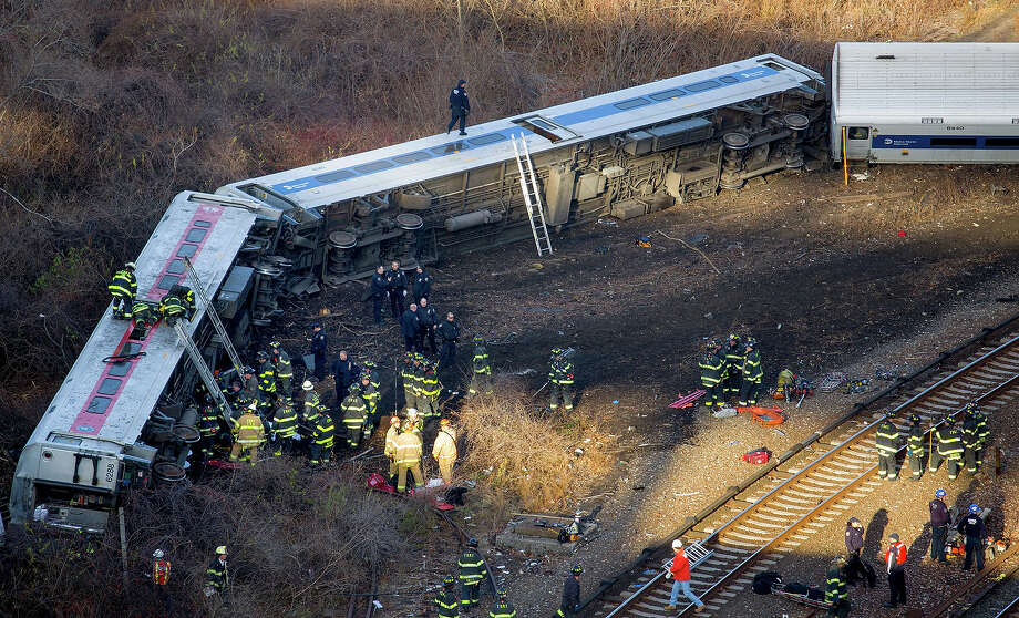 First responders work the scene of a derailment of a Metro-North passenger train in the Bronx borough of New York Sunday, Dec. 1, 2013. The train derailed on a curved section of track in the Bronx, coming to rest just inches from the water and causing multiple fatalities and dozens of injuries, authorities said. Metropolitan Transportation Authority police say the train derailed near the Spuyten Duyvil station. Photo: Craig Ruttle, ASSOCIATED PRESS / AP2013