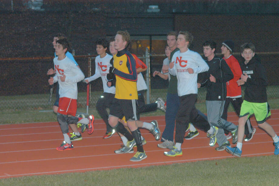 A group of New Canaan High School boys track team members run a lap outside during preseason practice. By Andy Hutchison Photo: Contributed Photo / New Canaan News