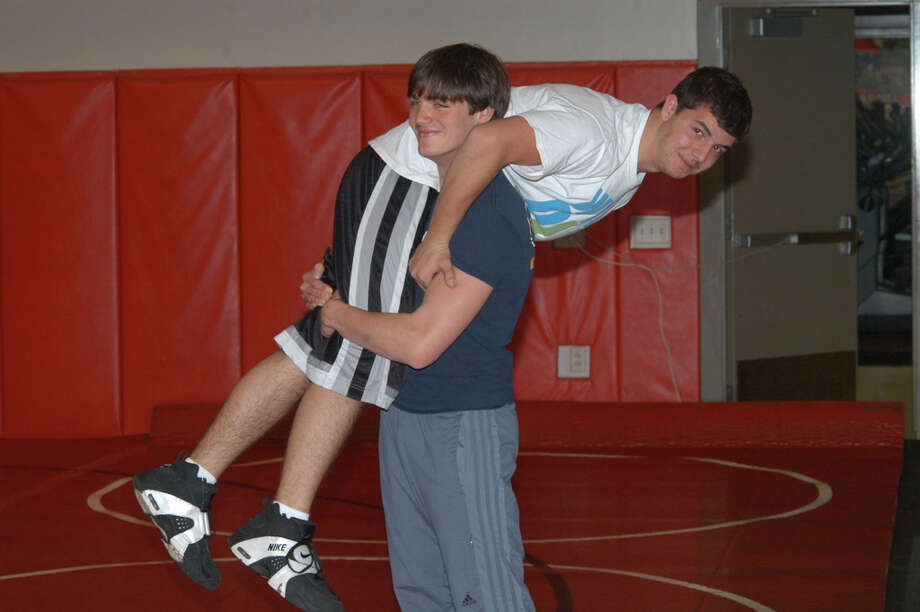 Wrestling captain Kenny Philipson (standing) is hoping to carry a lot of load for the inexperienced Rams this season, and Majro Halili is one of many up-and-coming grapplers this winter. By Andy Hutchison Photo: Contributed Photo / New Canaan News