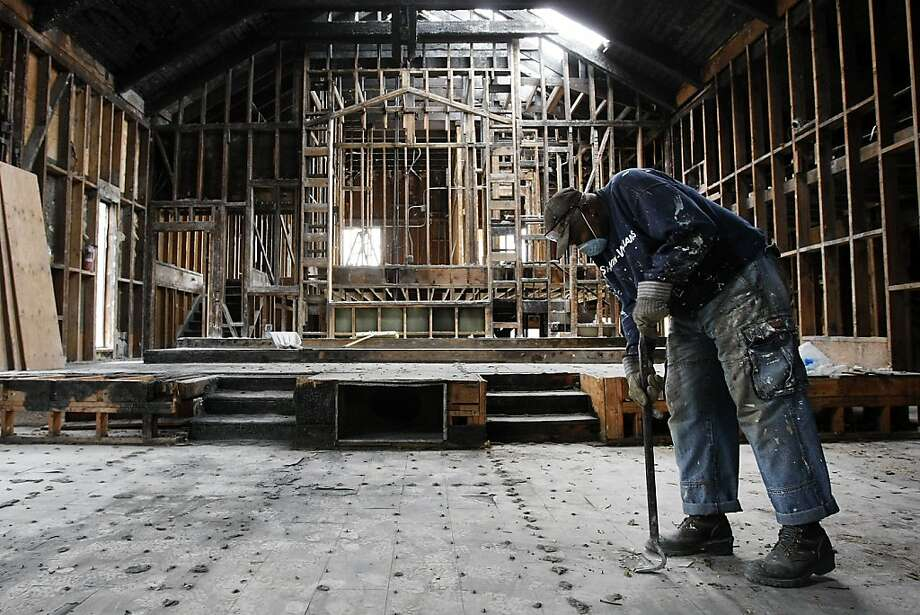 Donald Johnson of Oakland works in the sanctuary at Zion First Church of God in Christ, gutted by fire in September. Photo: Michael Short, The Chronicle