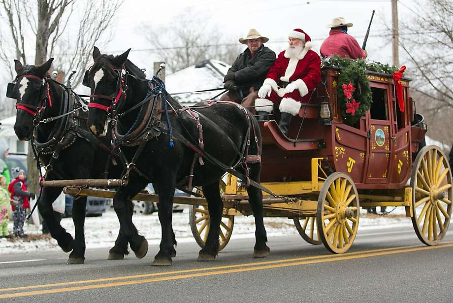 """Guess the reindeer are in the shop:Santa Claus rides a two-horse """"sleigh"""" during the White Lake Area Christmas   Parade in Whitehall, Mich. Photo: Natalie Kolb, Associated Press"""