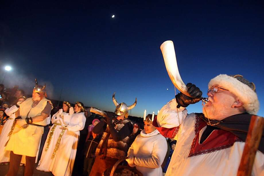 Fire up the ol' jule logs: Viking Brian Davis blows his horn after the lighting of the ceremonial bonfire at the Julefest celebration, a 