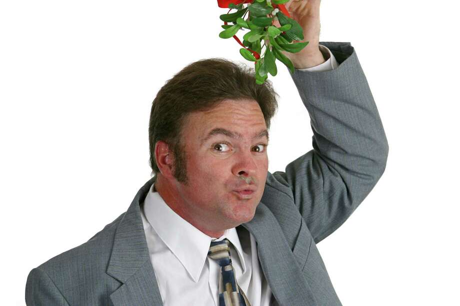 A guy at the office party holding mistletoe over his head and puckering up for a kiss. (Fotolia) Photo: Lisa F. Young / Lisa F. Young - Fotolia
