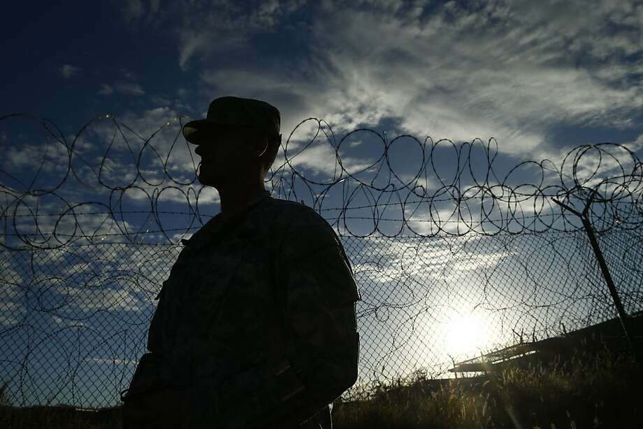 A soldier stands guard at Guantanamo Bay, where detainees were subjected to genital searches. Photo: Charles Dharapak, Associated Press
