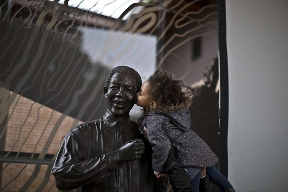 Bronz buss:A girl held by her mother kisses a statue of former president Nelson Mandela at  the Centre of Memory named for the South African leader in Johannesburg. Photo: Muhammed Muheisen, Associated Press