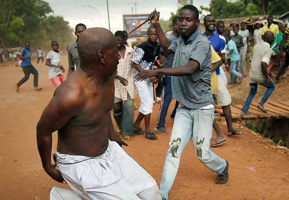 Mob justice:A Christian man wielding a dagger chases a suspected Seleka officer, dressed in civilian clothes, near the airport in Bangui, Central African Republic. French troops prevented the mob from hanging the man. Both Christian and Muslim mobs went on lynching sprees as French peace keepers deployed in the capital. Photo: Jerome Delay, Associated Press