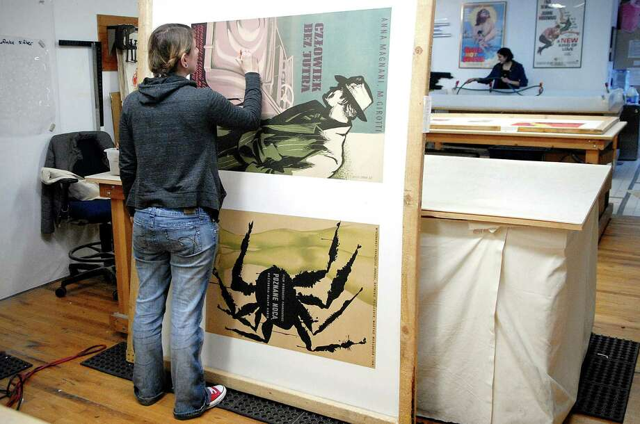 Angela Losquadro retouches a poster at Poster Conservation in Stamford, Conn. on Monday December 9, 2013. The shop mounts vintage posters on linen backing and restores them for galleries and individuals. Photo: Dru Nadler / Stamford Advocate Freelance