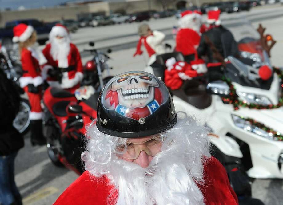 His glowing-eye skull helmet knows if you've been bad or good: Larry Daniels joins over a dozen biker Santa Clauses who arrived by motorcycle in York, Pa., to hand out stuffed animals to children. Photo: Jason Plotkin, Associated Press