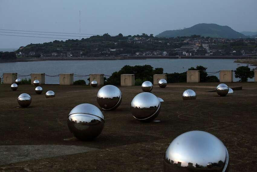 A memorial for those who died of or were sickened by mercury poisoning rests on a hill overlooking Minamata, Japan, in 2007.