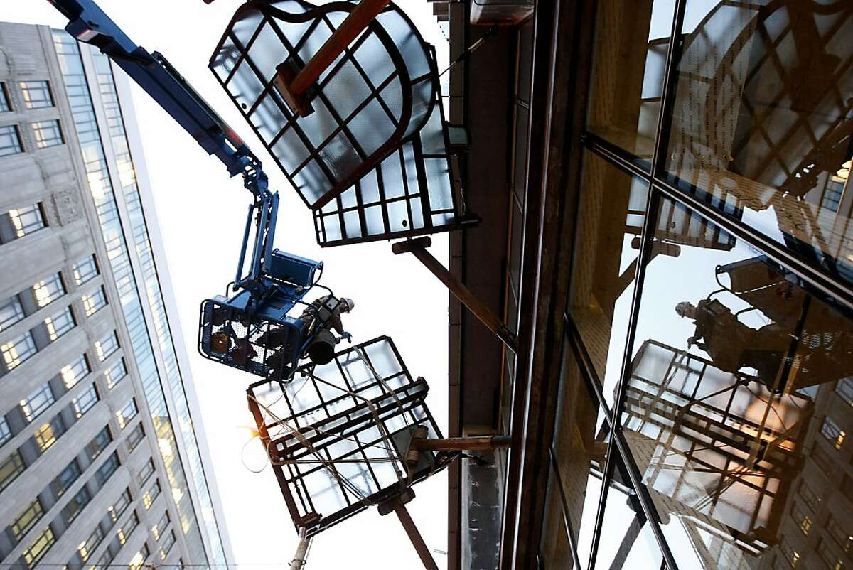 Artist Brian Goggin works on the installation of his newest public art piece entitled Caruso's Dream, which consists of series of glass-and-steel pianos suspended over the sidewalk of Avalon Bay, a new development that opens in February, in San Francisco, CA, Saturday, December 7, 2013.