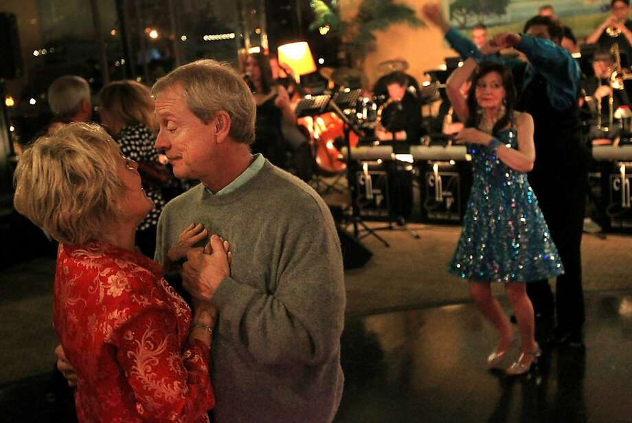 Gretchen Lukaszewski (left) sings along to the Chops Big Band as she dances with Gary Schlagenhauf at the Terrace Room in Oakland. The 18-piece band is made up of former band geeks happy to play for free. Photo: Leah Millis, The Chronicle