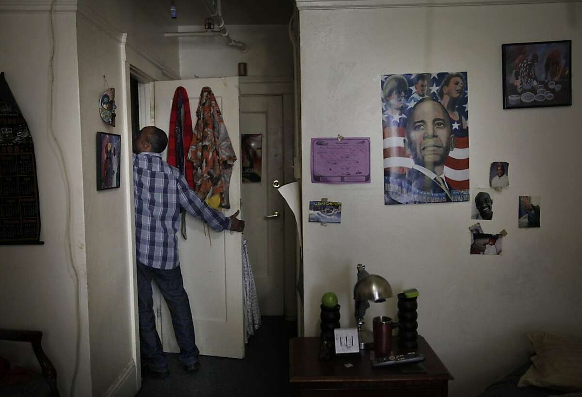 Donnel Fuller of San Francisco retrieves belongings from his closet in his room at the Senator Hotel on Thursday, November 14, 2013 in San Francisco, Calif.