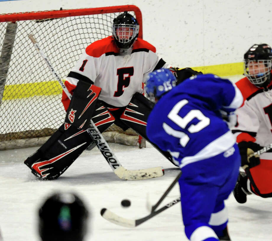 Fairfield Warde/Ludlowe goalie #1 Connor Frawley tracks a shot by Darien's #15 Craig Miller, during boys hockey action at the Wonderland of Ice in Bridgeport, Conn. on Saturday January 12, 2013. Photo: Christian Abraham / Connecticut Post
