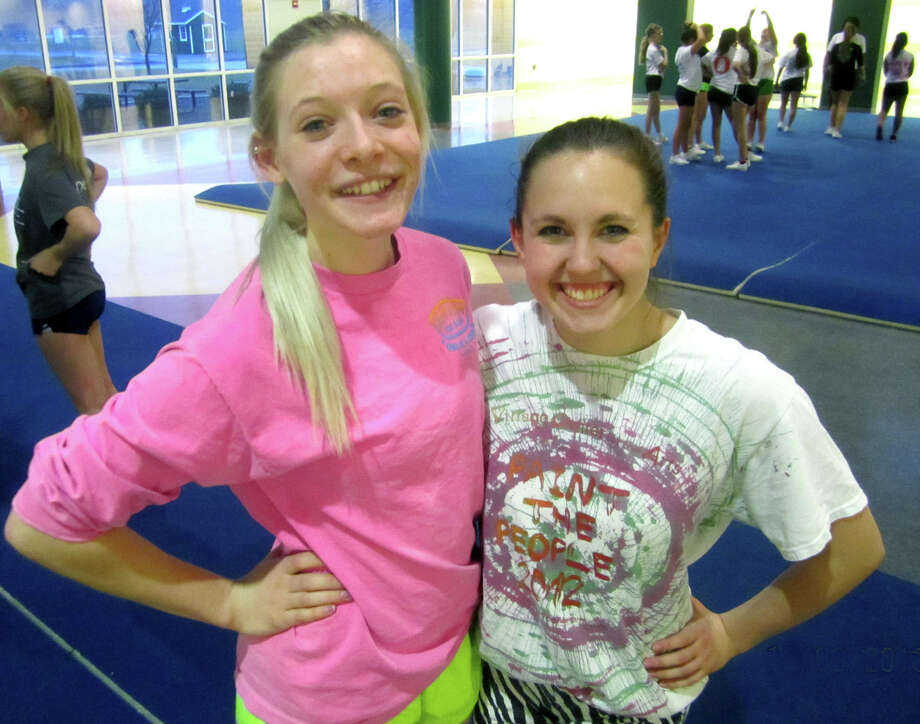 Janna Stratman, left, and Meghan Timan happily shoulder the responsibility of captaining the New Milford High School cheerleading team this winter. Dec. 9, 2013 Photo: Norm Cummings / The News-Times