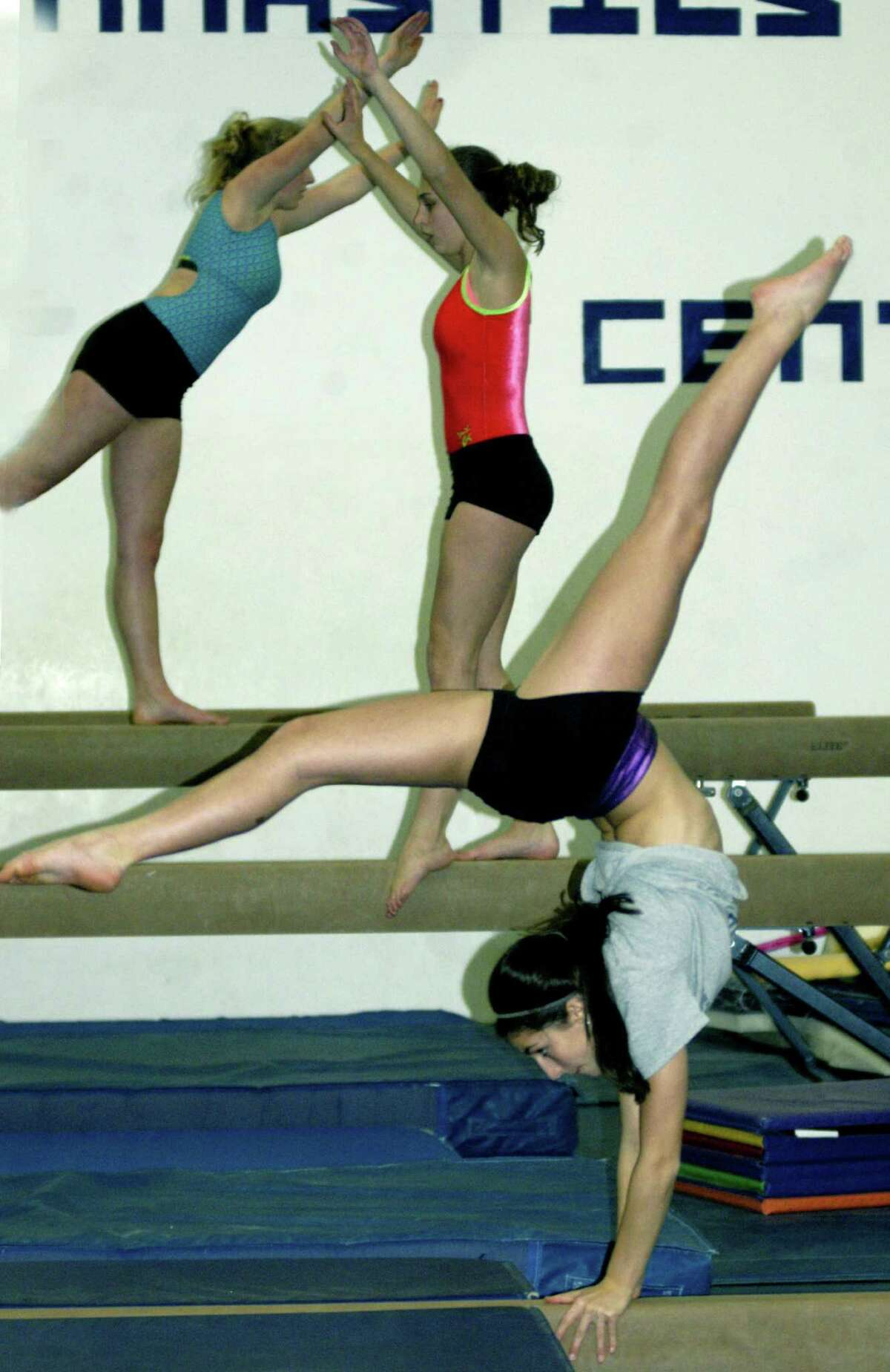 Green Wave athletes Emory Fairchild, foreground, Kalee Oelgoetz and Brianna Rutz practice their respective balance beam routines for New Milford High School gymnastics during practice at Elite Gymnastics. Dec. 5, 2013