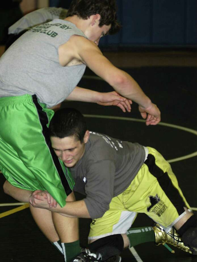 The Green Wave's talented Halim Bourjeli takes down teammate Jacob Plancon during pre-season practice for the perennially strong New Miiford High School wrestling team. Dec. 5, 2013 Photo: Norm Cummings / The News-Times