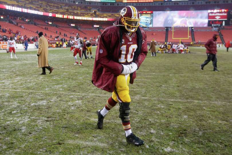 Washington Redskins quarterback Robert Griffin III walks off the field after an NFL football game ag