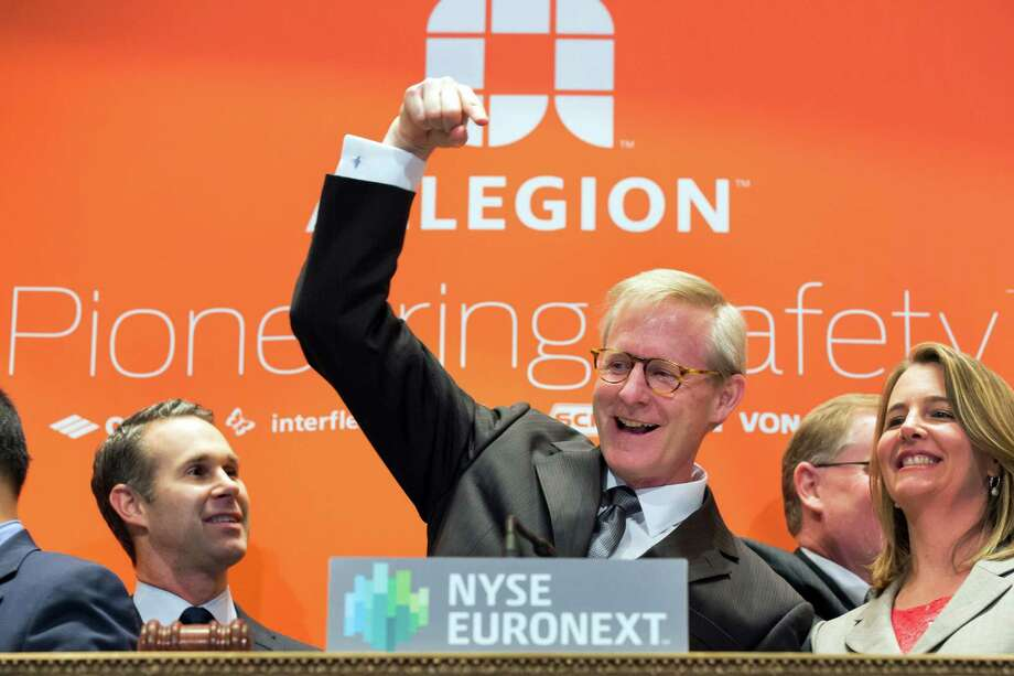 In this photo provided by the New York Stock Exchange, Allegion Chairman, President and CEO Dave Petratis, center, rings the New York Stock Exchange opening bell as his company's stock makes its debut as a standalone, publicly-traded company following its spinoff from Ingersoll Rand, Monday, Dec. 9, 2013.  (AP Photo/NYSE, Ben Hider) ORG XMIT: NYRD111 Photo: Ben Hider / New York Stock Exchange