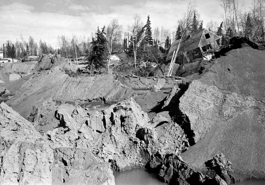 The nearly-completed six-story Four Seasons apartment building just off L Street in Anchorage, Alaska, lies in ruins after The Great Alaska Earthquake, but a home beside it appears undamaged, March 28, 1964. With a magnitude of 9.2, it was the most powerful earthquake in U.S. history, and despite recent powerful quakes, remains the second largest on record. Photo: Anonymous, Associated Press / AP1964