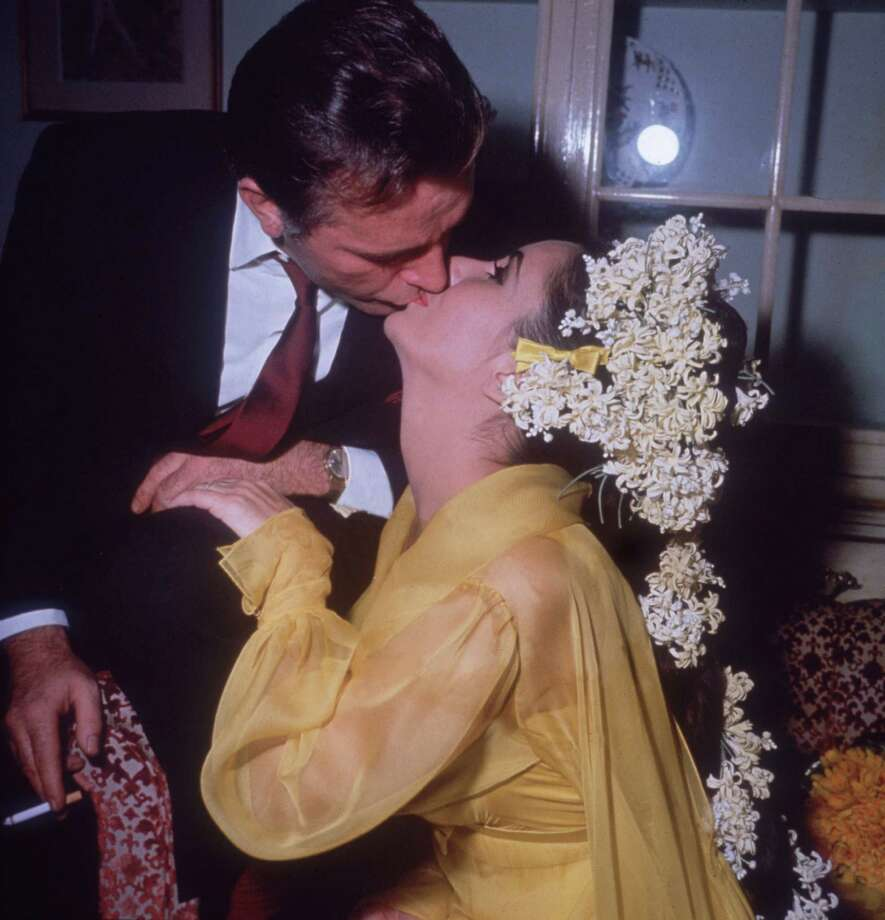 Actress Elizabeth Taylor sits on a sofa kissing her fifth husband, actor Richard Burton, while he leans over her on their first wedding day, March 15, 1964. Taylor is wearing a yellow gown and has flowers in her hair. Photo: Hulton Archive, Getty Images / Archive Photos