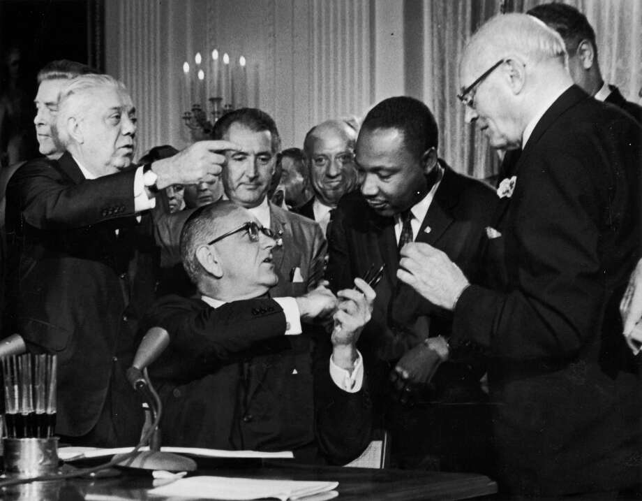 President Lyndon B. Johnson shakes the hand of Dr. Martin Luther King Jr. at the signing of the Civil Rights Act while officials look on, July 2, 1964, in Washington DC. Photo: Hulton Archive, Getty Images / 2003 Getty Images