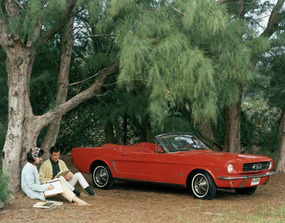 "Promotional shot of a red 1964 Ford Mustang convertible parked in a forest clearing with a couple sitting by a pinetree, 1964. This first series of the popular pony car is generally referred to as ""1964 1/2 Mustangs,"" because they were not rolled out in October of 1963 with the rest of the new 1964 Ford cars. Photo: FPG, Getty Images / 2005 Getty Images"