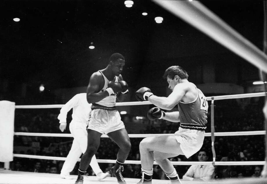American boxer Joe Frazier fells his German opponent Hans Huber in the Olympic Super Heavyweight Boxing Final at the Korakuen Ice Palace during the 1964 Tokyo Olympics on Oct. 21, 1964. Frazier, fighting with a broken right hand, won the gold medal despite a split judges decision. Photo: Keystone, Getty Images / 2004 Getty Images