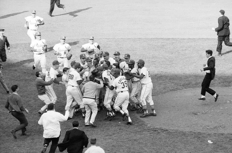 Bob Gibson of the St. Louis Cardinals is mobbed by his teammates after winning Game 7 of the 1964 World Series against the  New York Yankees on Oct. 15, 1964, in St. Louis, Mo. The loss was the end of a dynasty for the Yankees, who had played in 29 World Series over a period of 45 years. Photo: Herb Scharfman/Sports Imagery, Getty Images / 1964 Herb Scharfman/Sports Imagery