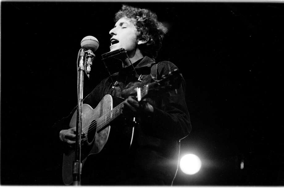 "Bob Dylan performs at an afternoon ""workshop"" session, July 1, 1964. Photo: Douglas R. Gilbert, Getty Images / Redferns"