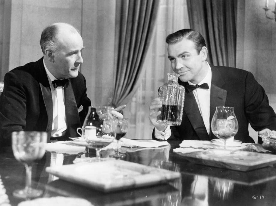 "Sean Connery smells liquor in a carafe while sitting a a dining table with an unknown actor of in a scene from the film ""Goldfinger,"" 1964. Photo: Archive Photos, Getty Images / 2011 Getty Images"