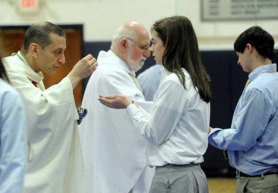 Bishop Frank J. Caggiano, bishop of the diocese of Bridgeport, Conn. serves communion to Maeve Reilly during Mass at Immaculate High School in Danbury, Conn. Monday, Dec. 9, 2013. Photo: Carol Kaliff / The News-Times