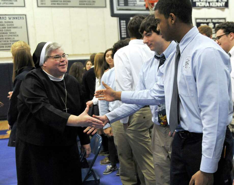 Sister Mary Grace Walsh, superintentent of schools for the diocese of Bridgeport, Conn. greets students during a Mass celebrated by  Bishop Frank J. Caggiano, at Immaculate High School in Danbury, Conn. Monday, Dec. 9, 2013. Photo: Carol Kaliff / The News-Times