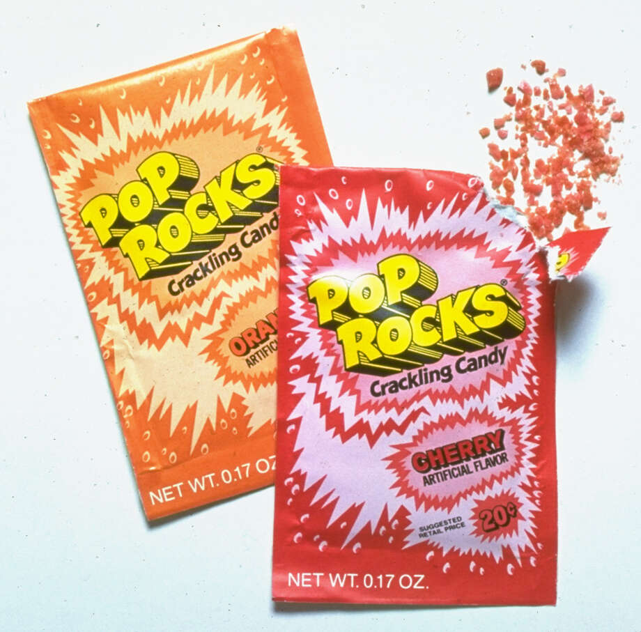 Two packages of flavored Pop Rocks are displayed with some of the crackling candy. The urban legend that eating Pop Rocks and drinking soda would cause a person's stomach to blow up persists to this day. Photo: Al Freni, Getty Images / Al Freni