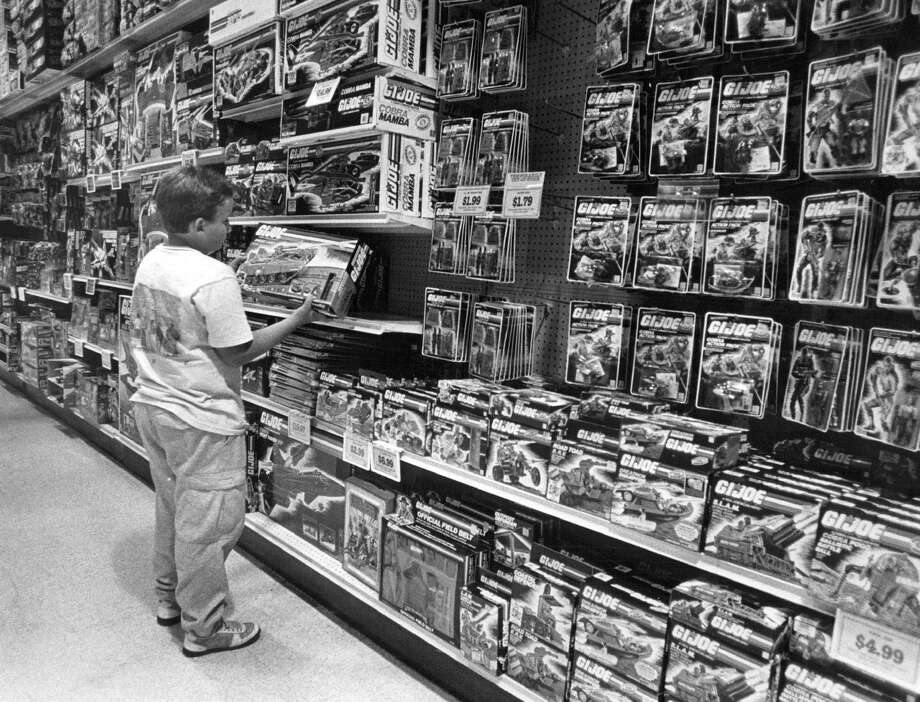 Sean Hill, 10, looks at a G.I. Joe at Children's Palace in Littleton, Colo., in 1987. In 1974, the iconic action figure was given kung fu grip as part of the martial arts craze of the 1970s. Photo: John Prieto, Getty Images / (C) 2010 The Denver Post, MediaNews Group