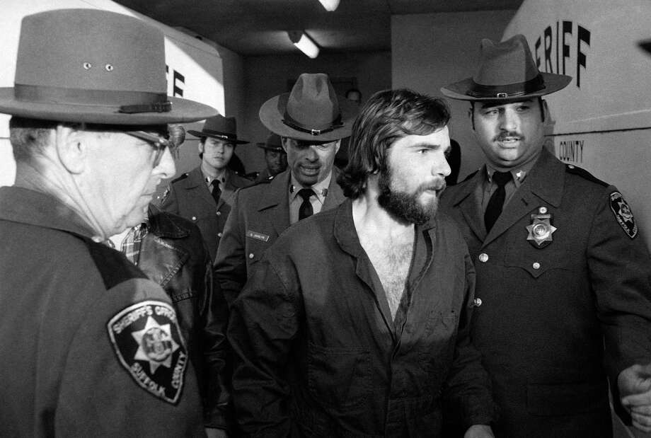"Ronald DeFeo Jr. (center) leaves Suffolk County, N.Y., District Court after a hearing on Nov. 15, 1974, after his arrest in the slayings of his parents, two brothers and two sisters on early Nov. 13 at their home in Amityville, N.Y. The six were shot to death in their sleep. The case, in which DeFeo was convicted and sentenced to six terms of 25 years to live, was the inspiration for the book and film versions of ""The Amityville Horror."" Photo: Richard Drew, Associated Press / 1974 AP"