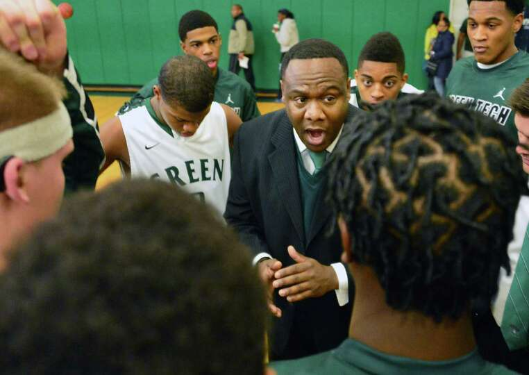 Green Tech head coach Jamil Hood Sr., center, with his players during Saturday's game with East High