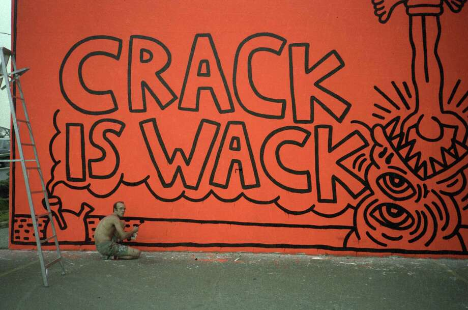 "American pop artist and activist Keith Haring paints the original version of his ""Crack is Wack"" mural on the wall of a hand ball court in a public park at East 128th Street and 2nd Avenue, alongside Harlem River Drive in New York City in the summer 1986. Crack cocaine usage soared in the United States beginning in 1984. Photo: Juan Rivera/Roulette Fine Art, Getty Images / Archive Photos"