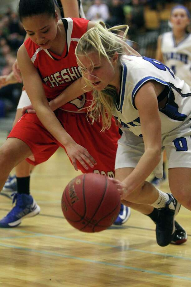 Darien High School player Kelly Karczewshi fends off Cheshire opponent Bry McIntosh during CIAC basketball action in Darien on Tuesday evening.© J. Gregory Raymond for The Advocate Photo: J. Gregory Raymond / Stamford Advocate Freelance;  © J. Gregory Raymond