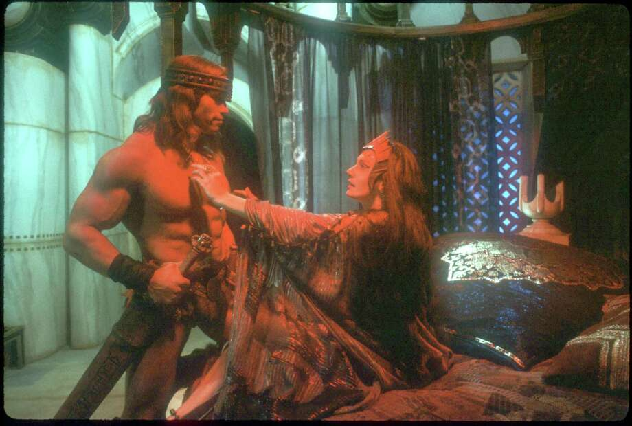 "Actors Arnold Schwarzenegger and Sarah Douglas as Conan and Queen Taramis rehearse a scene in ""Conan the Destroyer,"" in January 1984. Photo: Dirck Halstead, Getty Images / Hulton Archive"
