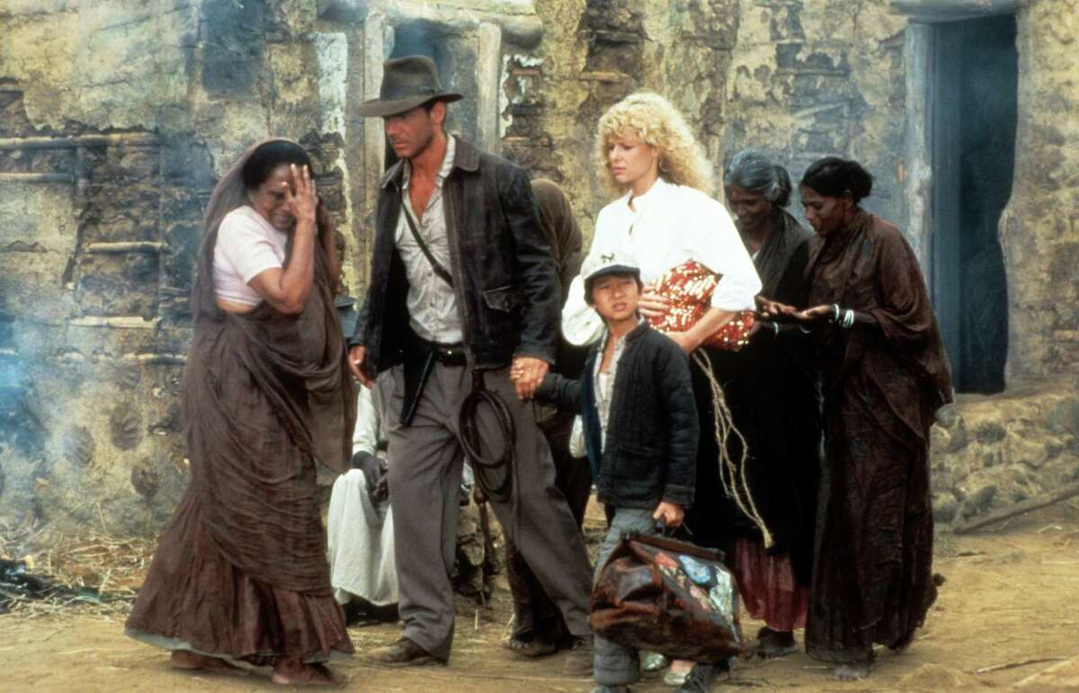 Harrison Ford, Jonathan Ke Quan and Kate Capshaw are lead through a temple in a scene from the film