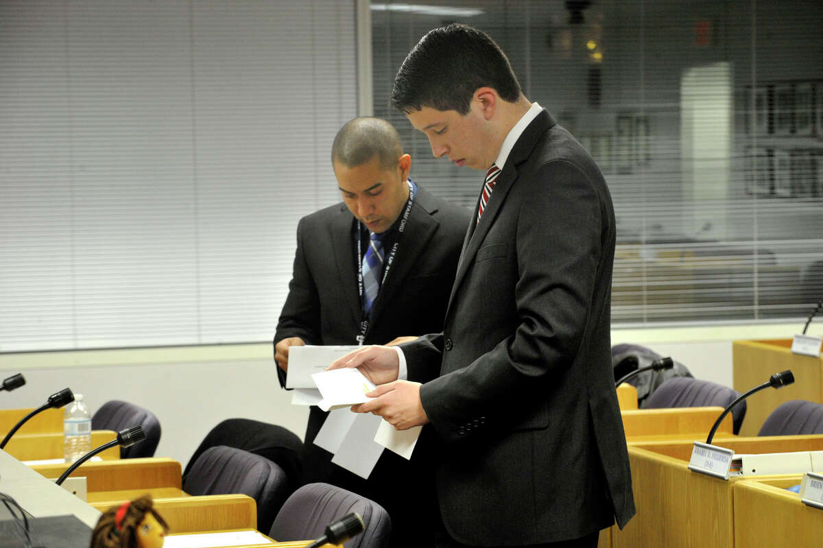 Newly elected members of the Stamford Board of Representatives from District 16 Matthew Quinones, left, and Steven Kolenberg look over paperwork before their meetings in the legislative chamber at the Stamford Government Center on Monday, Dec. 9, 2013. Quinones and Kolenberg are part of handful of Board of Reps elected this year that are under the age of 35.