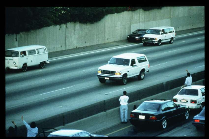 Motorists wave as police cars pursue the Ford Bronco driven by Al Cowlings, carrying fugitive murder suspect O.J. Simpson, on a 90-minute slow-speed car chase June 17, 1994, on the 405 freeway in Los Angeles. Four days earlier, Simpson's ex-wife Nicole Brown Simpson and Ronald Goldman were found murdered.